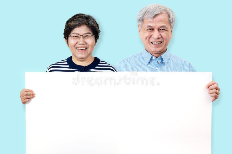 O vovô feliz e a avó que sorriem com dentes brancos, apreciam o momento e guardar uma placa vazia Avós asiáticas que mostram a pl imagens de stock royalty free