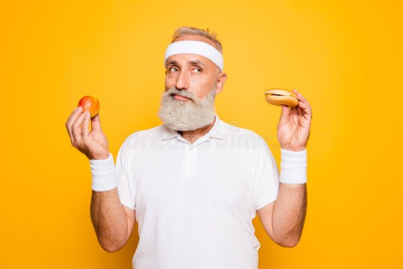 O vovô fresco do atleta guarda o cheeseburger proibido dos alimentos sem valor nutritivo e o f imagens de stock royalty free