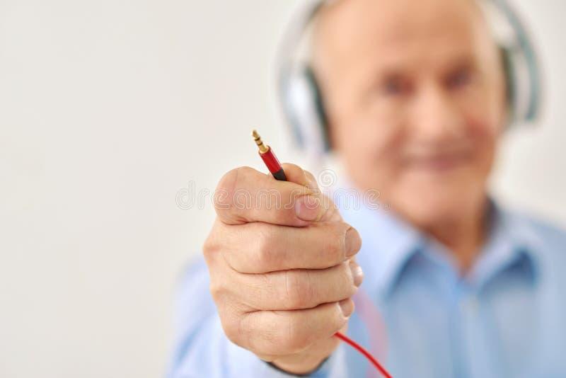 O vovô mantém o cabo dos auriculares fotos de stock royalty free