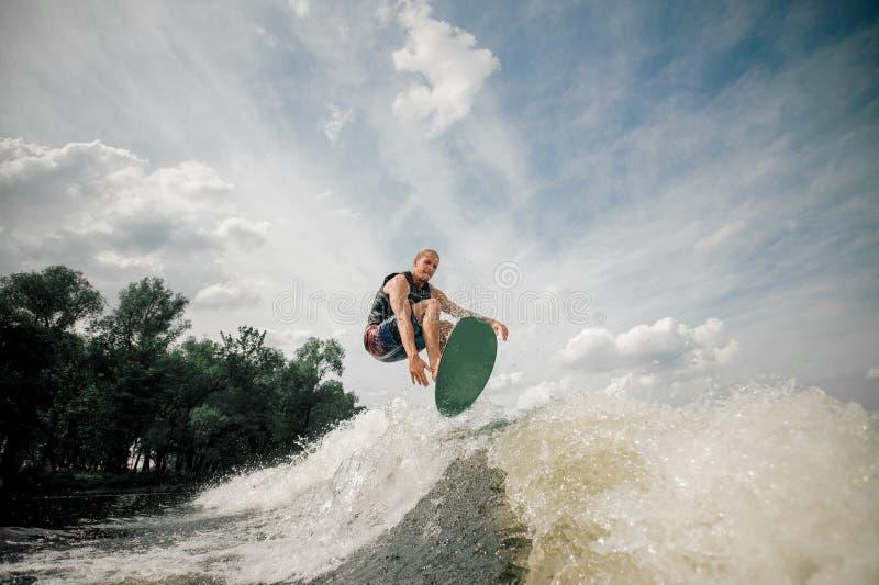 O Wakeboarder executa vários truques em um salto fotos de stock royalty free