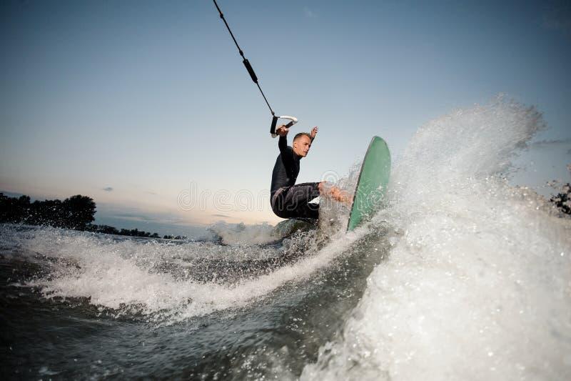 O wakesurfer ativo que monta abaixo das ondas azuis da elevação do rio com espirra imagem de stock