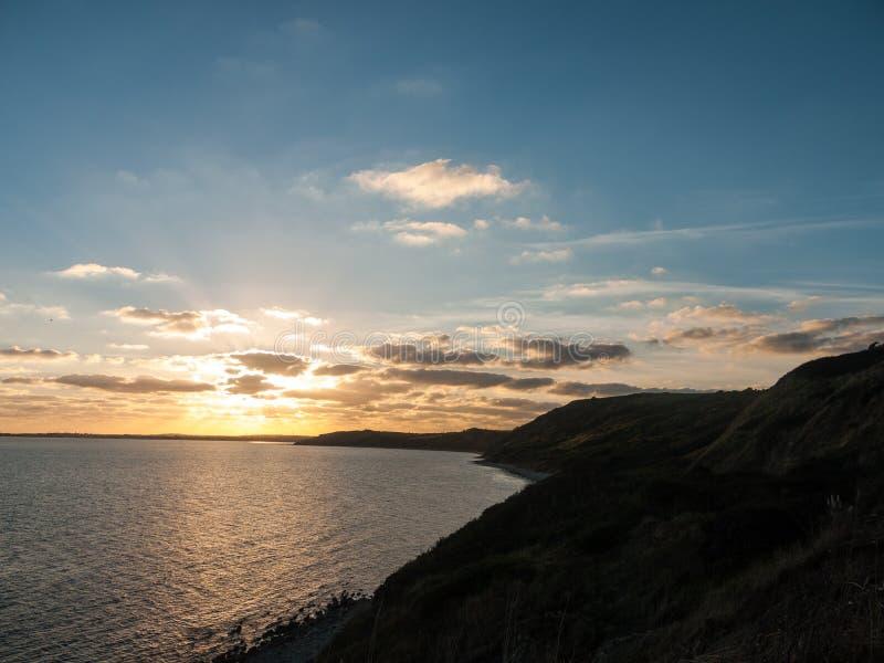o weymouth bonito Dorset do por do sol nubla-se o la da luz do mar da água do oceano imagem de stock