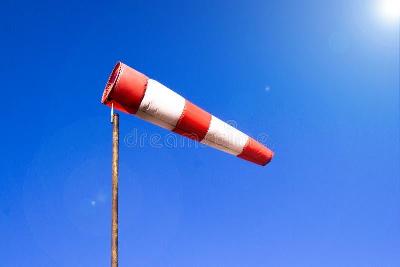 O windsock do aeroporto no fundo claro do c?u azul no tempo ventoso indica que a dire??o do vento local igualmente chamou: pe?ga  foto de stock