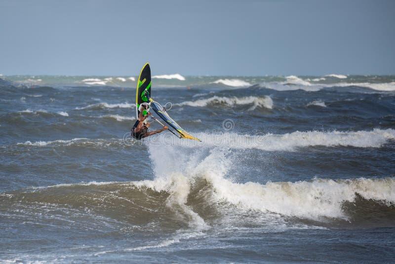 O Windsurfer salta da água: Stunting em ondas imagem de stock