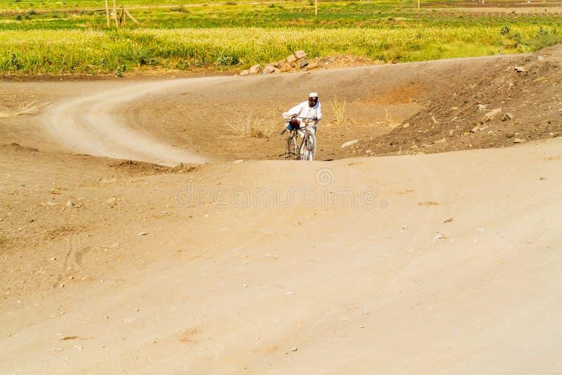 O wiyh do homem uma bicicleta na estrada em Sudão imagem de stock