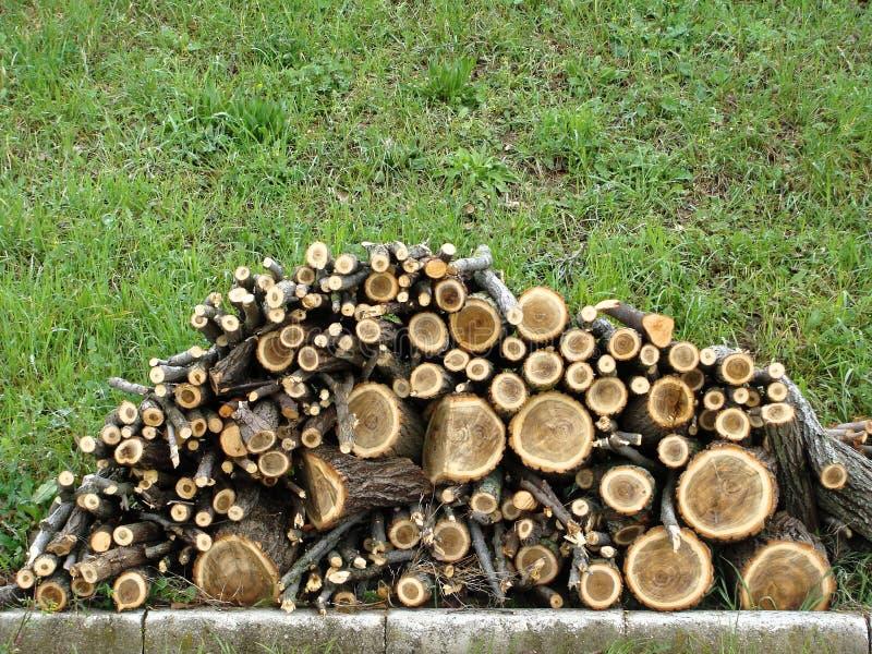O Woodpile com lenha é empilhado na grama na jarda da casa da quinta fotografia de stock