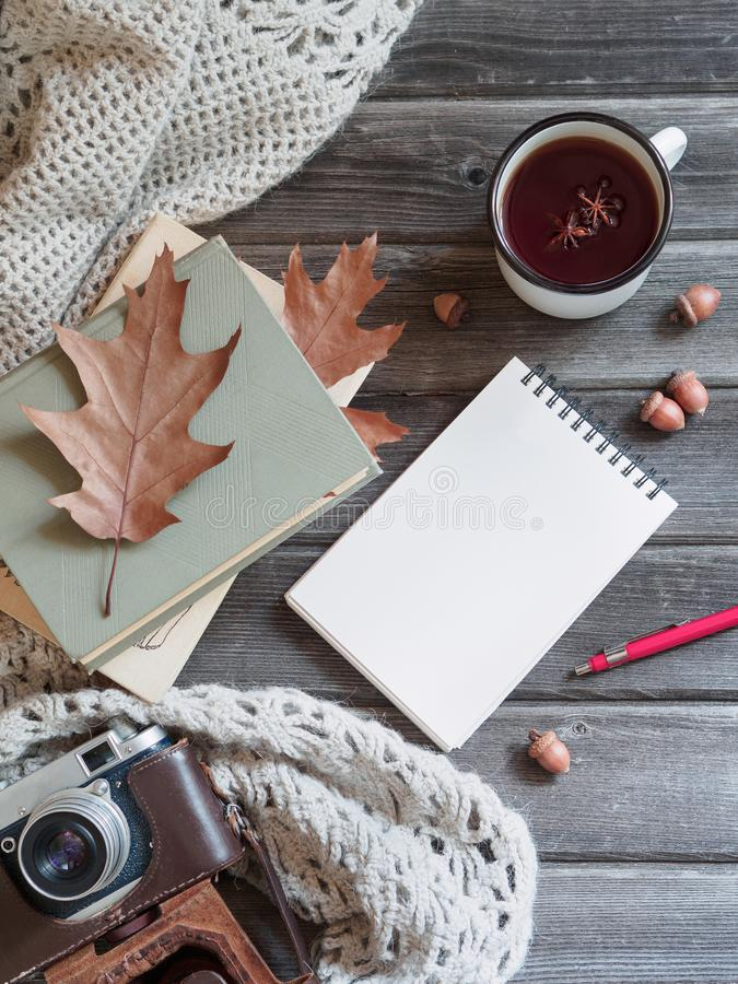 O xaile feito malha do fundo do outono tabela de madeira, câmera, carvalho sae do bloco de notas fotografia de stock