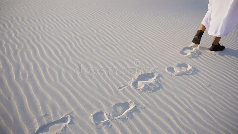 O xeique árabe masculino feliz anda ao longo do deserto e do rejo brancos da areia imagem de stock
