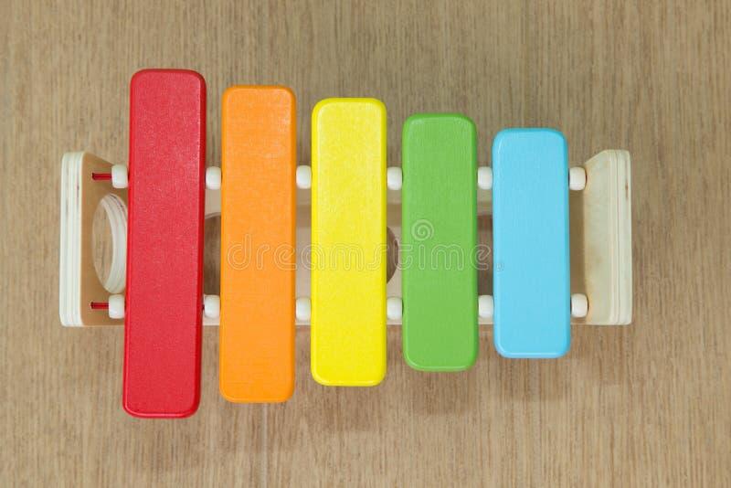 O xilofone de madeira multi-colorido das crianças está encontrando-se no assoalho perto do martelo fotos de stock