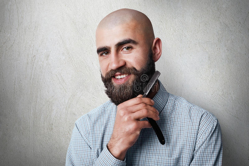 O yound atrativo balded o barbeiro com a barba preta grossa e o bigode que sorriem ao guardar a lâmina reta em sua barba Um cabel fotos de stock