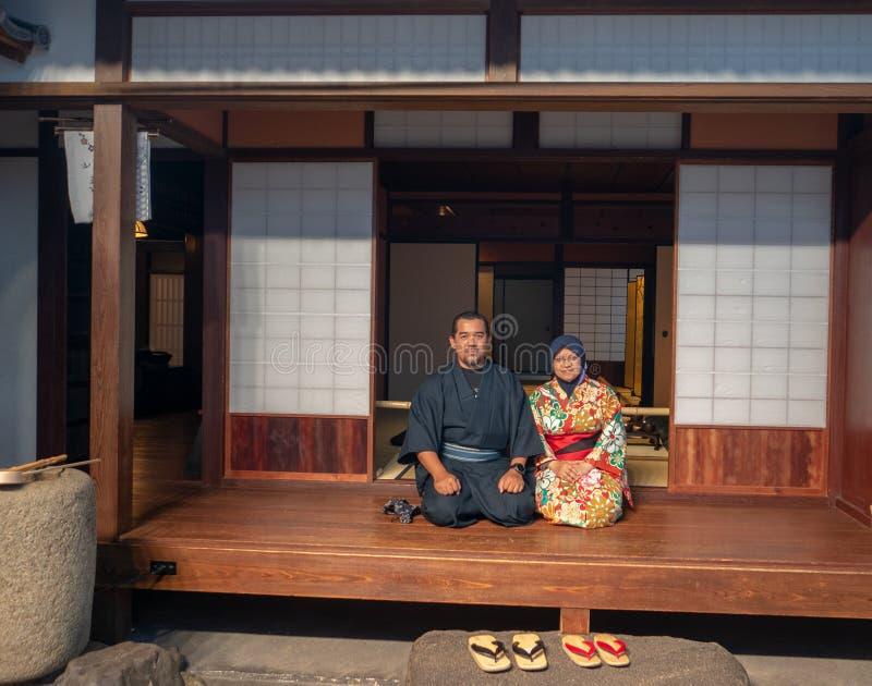 O yukata vestindo e o quimono dos pares muçulmanos não identificados levantaram na frente de uma casa japonesa em Osaka, Japão fotografia de stock