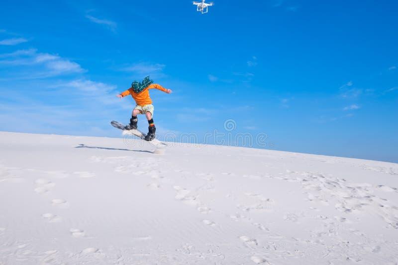 O zangão dispara em um homem que faça truques em um snowboard foto de stock royalty free