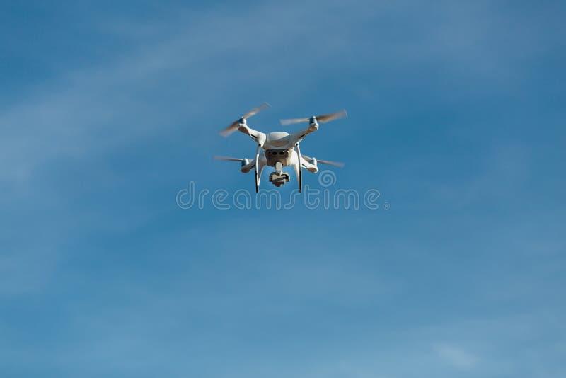 O zangão, helicóptero, quadrupter voa contra o céu azul Uma câmera a alta definição dispara em fotos imagem de stock royalty free