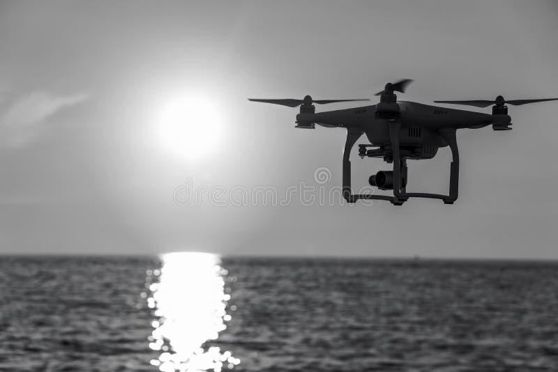 O zang?o no c?u do por do sol as montanhas da onda de oceano fecham-se acima do quadrocopter fora conceito para a videografia do  foto de stock