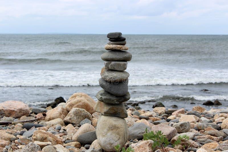 O zen gosta do jardim na praia, com diversas rochas equilibradas em uma outra perto da borda do mar imagem de stock