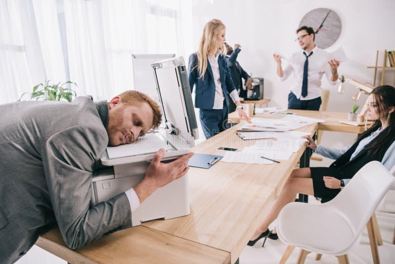 o zombi esgotado gostar do homem de negócios que dorme na copiadora quando seus colegas que têm a conversação imagens de stock