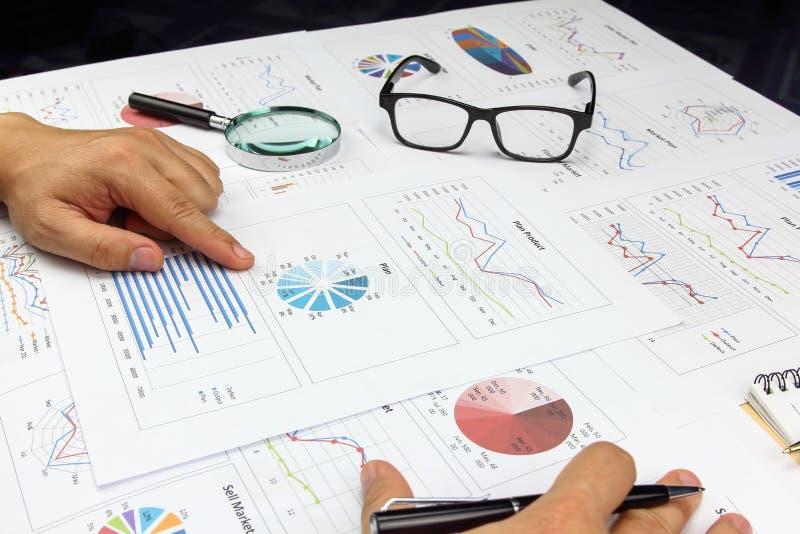 O zumbido da lupa do uso do homem de negócios e pensa analisa o gráfico fotos de stock