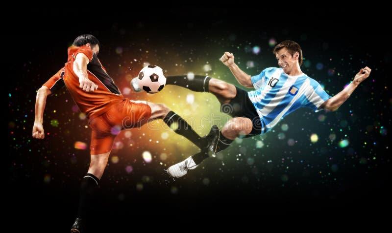 o Zwei Spieler in der Aktion, zum des Balls am Fußballspiel auf dunklem Hintergrund mit Lichtern zu treten und stockfotos