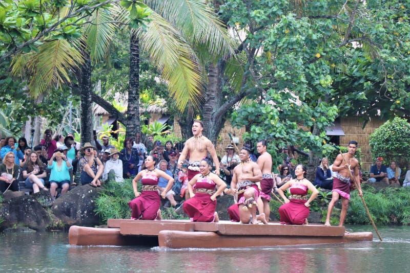 Oahu, Hawa? - 4/26/2018 - Hawaiiaanse dansers die terwijl het berijden van een kanovlotter op het Polynesische Culturele Centrum  stock foto