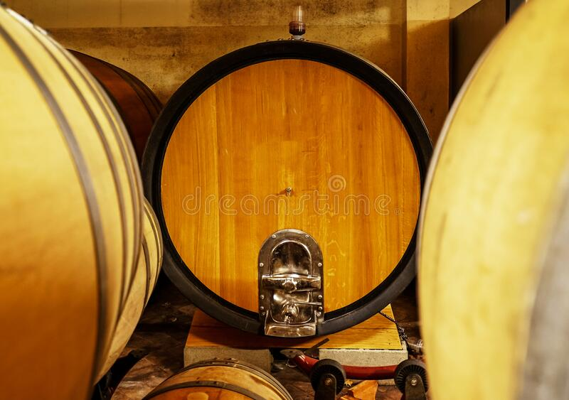 Oak barrels of wine in the basement of an Italian winemaker. Old wine production technology stock image