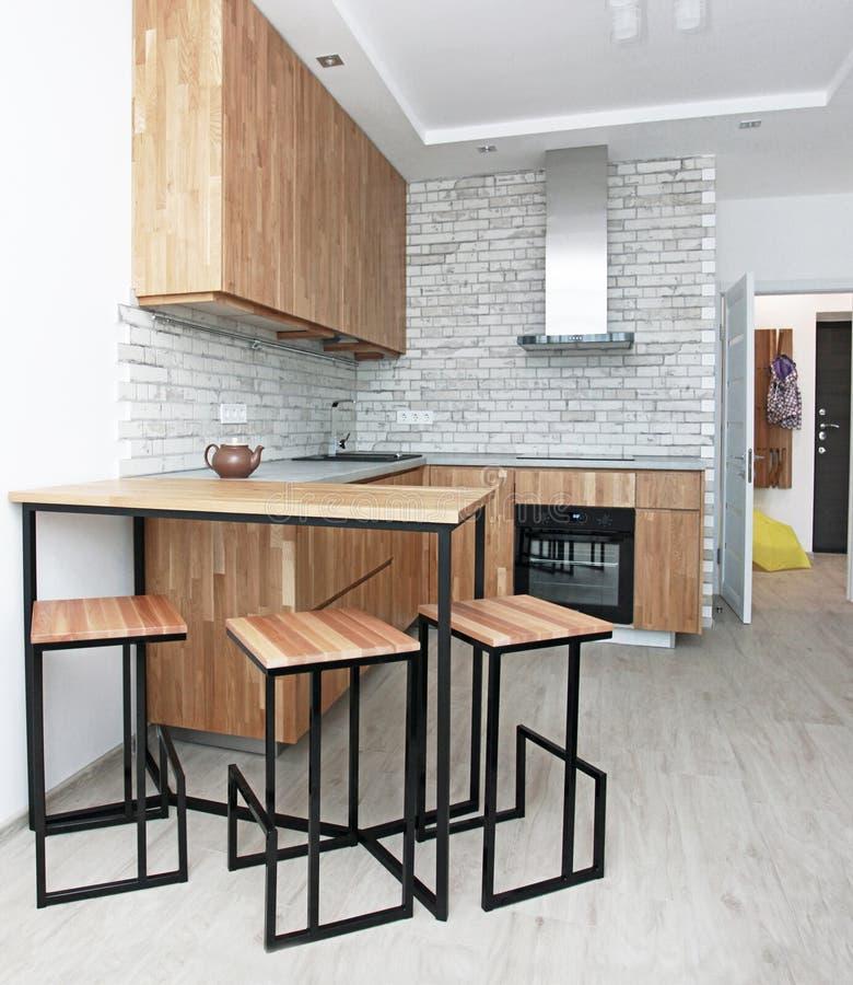 Oak-köket med bordsbord och en entréhall i den skandinaviska designen på eftermiddagen inre, minimalism, livsstil royaltyfri bild