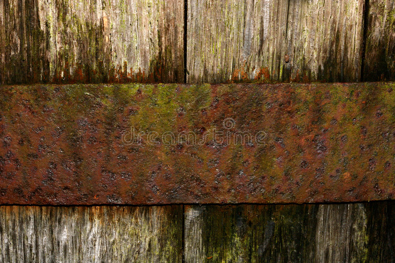 Oak and Rust. Section of an old oak whisky barrel, with a rusty band of metal holding the oak boards in place stock photo