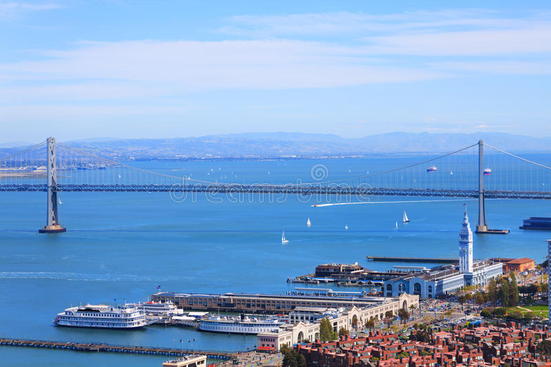 Oakland Bay Bridge in San Francisco and port tower. Oakland Bay Bridge in San Francisco and Port pier building with tower in downtown stock photography