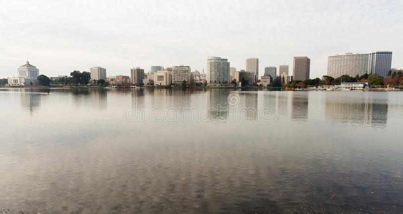Oakland California Afternoon Downtown City Skyline Lake Merritt. An overcast sky is reflected in the smooth water of Lake Merritt in front of Oakland and an royalty free stock photos