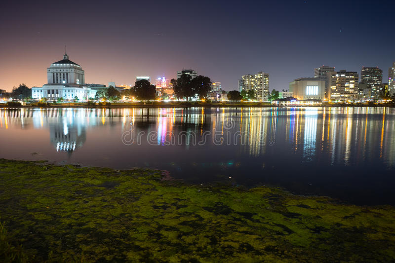 Oakland California Night Sky Downtown City Skyline Lake Merritt. Smooth water of Lake Merritt in front of Oakland royalty free stock photos