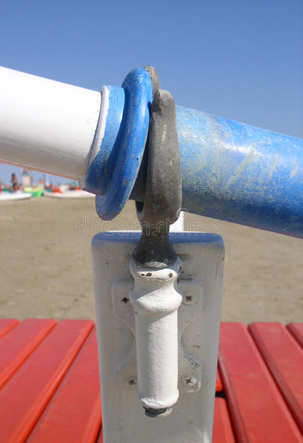 Oar and oarlock on the beach. Particular of a oarlock in the foreground on the beach stock photo