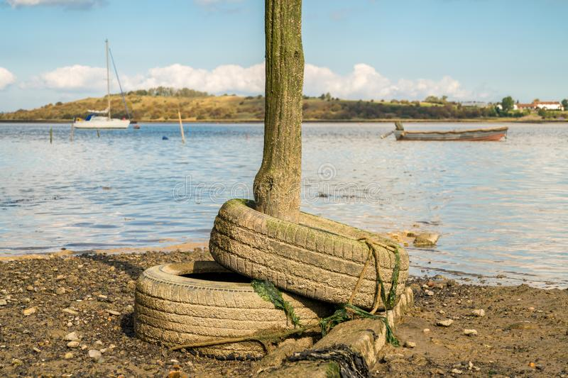Oare Marshes, near Faversham, Kent, England, UK. Old tyres and a wooden post in the Oare Marshes near Faversham, Kent, England, UK - with boats and the Isle of royalty free stock photo
