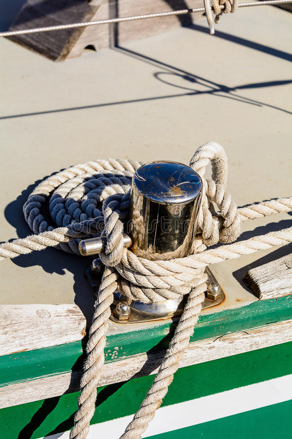 Oarlock and rope on a sailboat. Fragmentary view details of knots and ropes on the yacht moored in the dock royalty free stock photo
