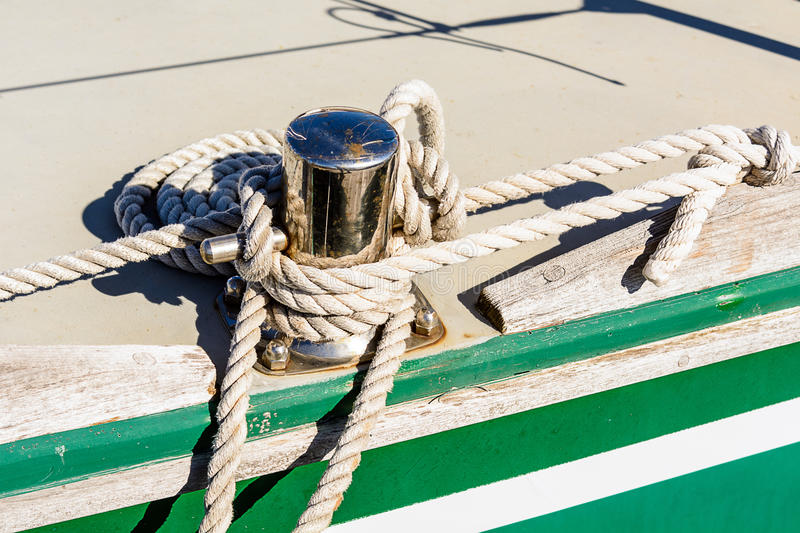 Oarlock and rope on a sailboat. Fragmentary view details of knots and ropes on the yacht moored in the dock royalty free stock photos