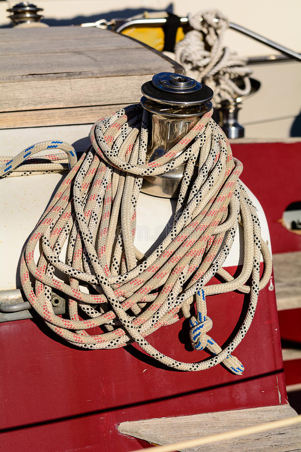 Oarlock and rope on a sailboat. Fragmentary view details of knots and ropes on the yacht moored in the dock. Oarlock and rope on a sailboat royalty free stock photography