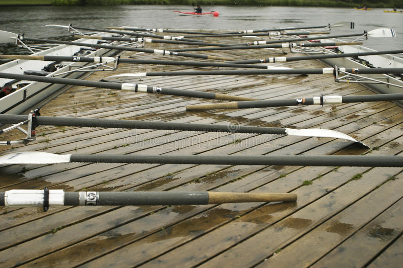 Oars On A Dock. Two racing shells by the dock with oars at rest prior to a rainy practice stock images