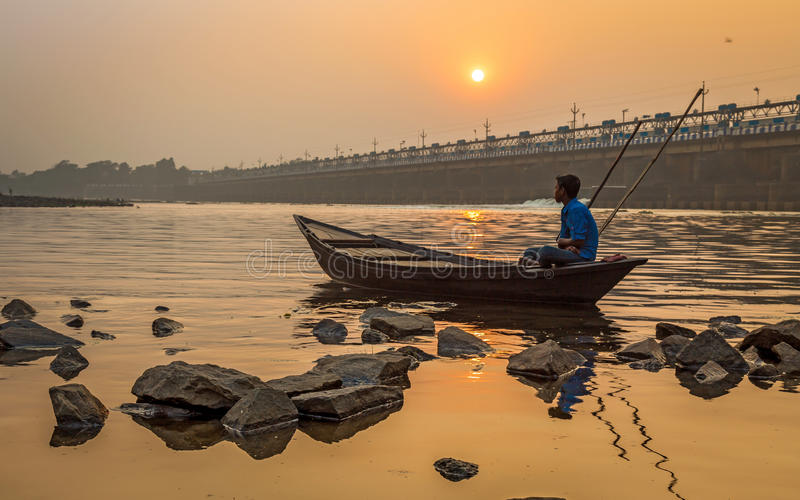 Oarsman sits on his boat to shore at sunset on river Damodar near the Durgapur Barrage. DURGAPUR, INDIA - DECEMBER 20, 2016: An oarsman sits on his boat to royalty free stock photo