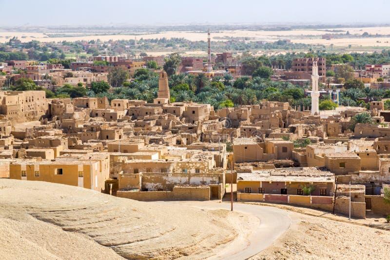 Oase mit Ruinen Alte nahöstliche arabische Stadt errichtet von den Schlammziegelsteinen, alte Moschee, Minarett Neue Stadt in der stockfotografie