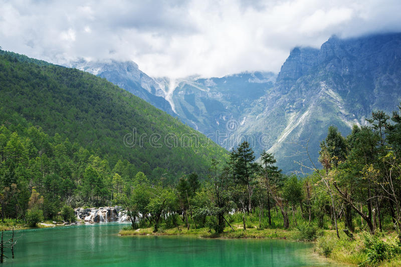 Oasis and peaks. Green mountains and plains filled my eyes, tall mountains and white clouds like background, the whole picture is very shocking, large tracts of royalty free stock photo