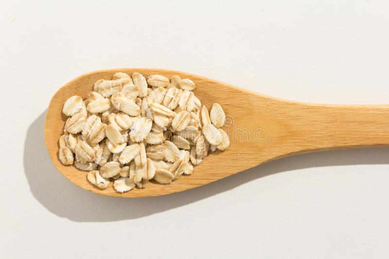 Oat cereal grain. Nutritious grains on a wooden spoon on white b stock photography