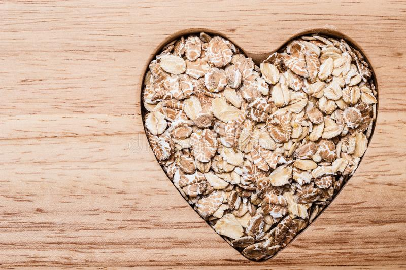 Oat cereal heart shaped on wooden surface. Dieting healthcare concept. Oat cereal oatmeal heart shaped on wooden surface. Healthy food for lowering cholesterol royalty free stock image