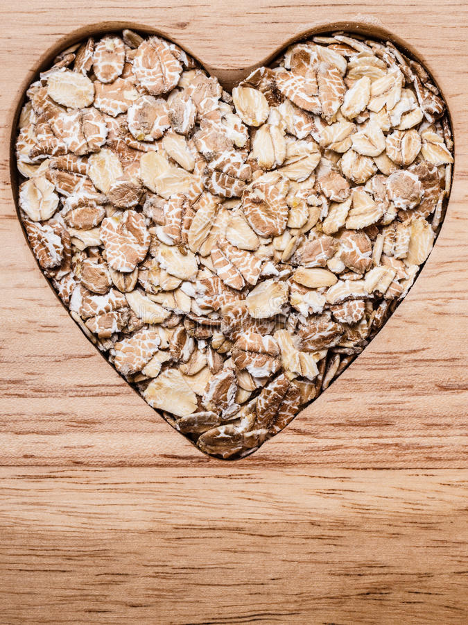 Oat cereal heart shaped on wooden surface. Dieting healthcare concept. Oat cereal oatmeal heart shaped on wooden surface. Healthy food for lowering cholesterol stock photo