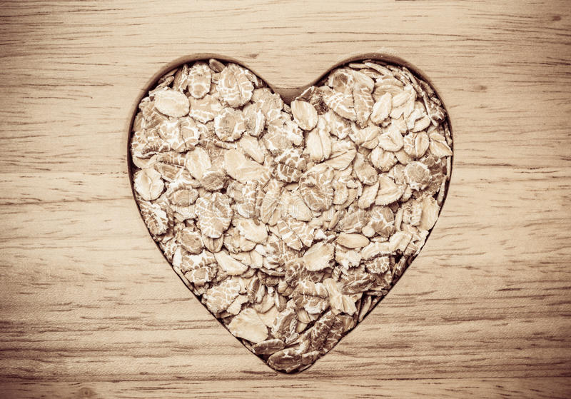 Oat cereal heart shaped on wooden surface. Dieting healthcare concept. Oat cereal oatmeal heart shaped on wooden surface. Healthy food for lowering cholesterol stock image