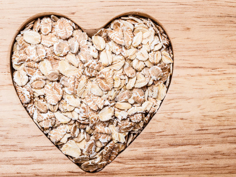 Oat cereal heart shaped on wooden surface. Dieting healthcare concept. Oat cereal oatmeal heart shaped on wooden surface. Healthy food for lowering cholesterol royalty free stock photography
