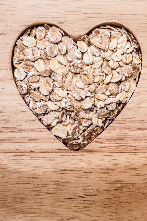 Oat cereal heart shaped on wooden surface. Dieting healthcare concept. Oat cereal oatmeal heart shaped on wooden surface. Healthy food for lowering cholesterol royalty free stock images