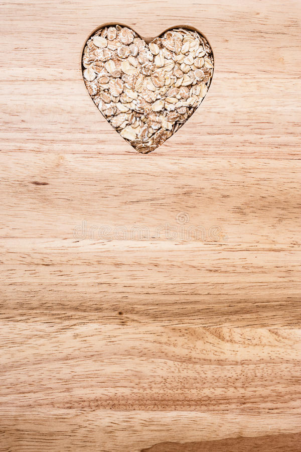 Oat cereal heart shaped on wooden surface. Dieting healthcare concept. Oat cereal oatmeal heart shaped on wooden surface. Healthy food for lowering cholesterol stock photography