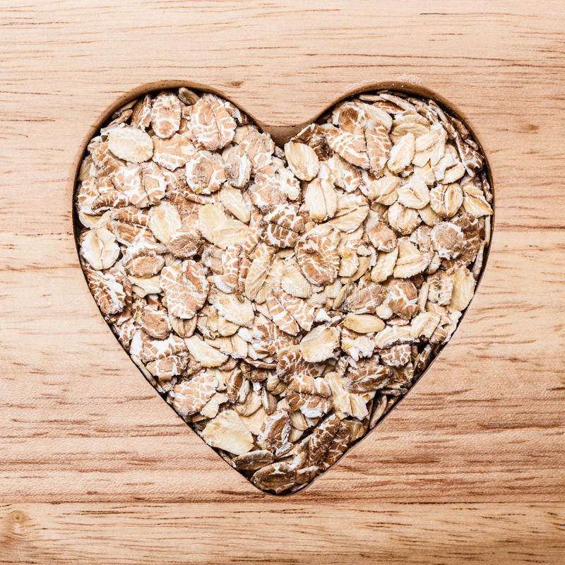 Oat cereal heart shaped on wooden surface. Dieting healthcare concept. Oat cereal oatmeal heart shaped on wooden surface. Healthy food for lowering cholesterol stock photos