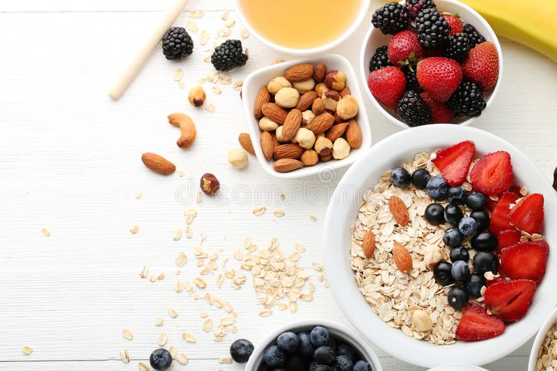 Oat flakes with berries. And nuts on wooden table stock photo