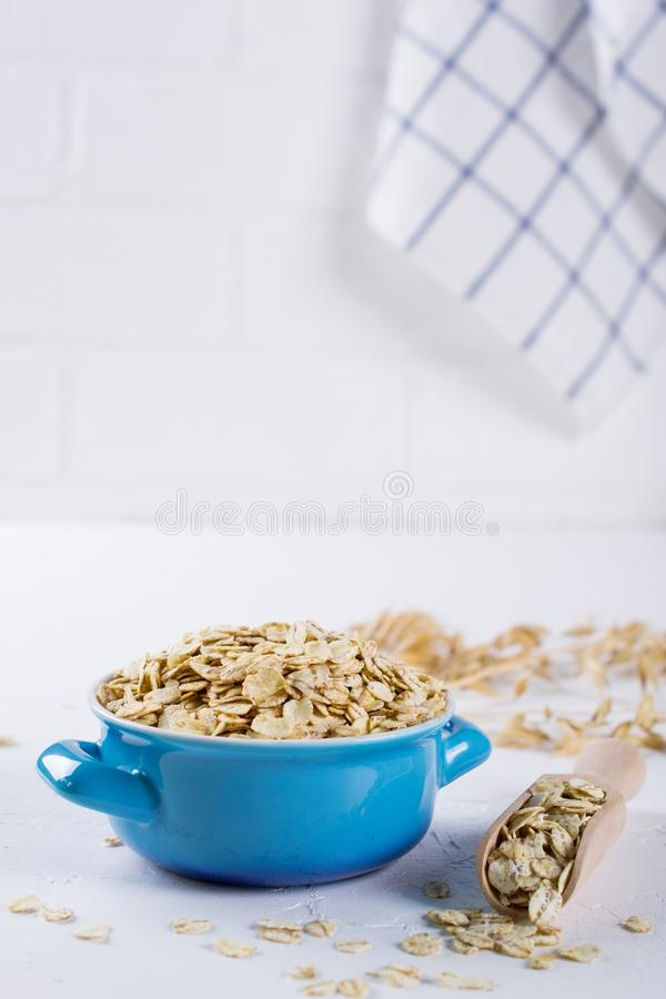 Oat flakes in blue bowl on the kitchen table. Healthy breakfast concept stock photo