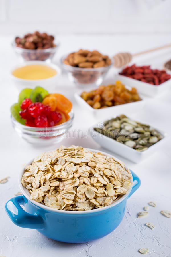 Oat flakes in blue bowl and various delicious ingredients for healthy breakfast on the kitchen table. royalty free stock photo