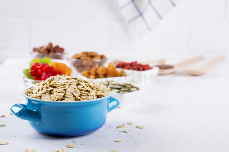 Oat flakes in blue bowl and various delicious ingredients for healthy breakfast on the kitchen table. Healthy breakfast stock image
